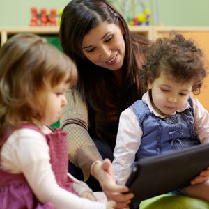 Quizler Preschool Banner Teacher Sits With Kids And Tablet