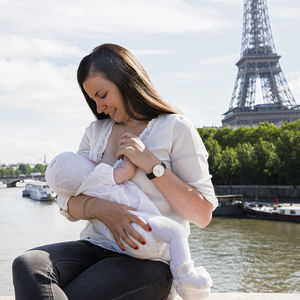 woman breastfeeding in front of eiffel tower