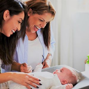 Hispanic grandmother and daughter playing with grandchild on changing table