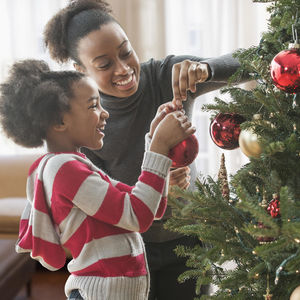 Holiday traditions: Mother and daughter decorating Christmas tree