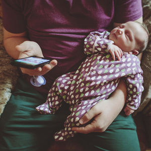 Father with his baby girl using a smart phone