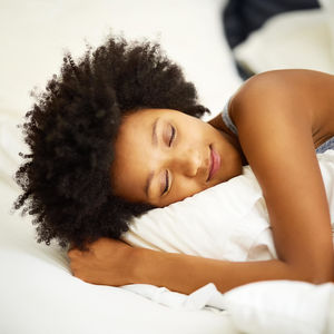 how to sleep better: woman sleeping in bed