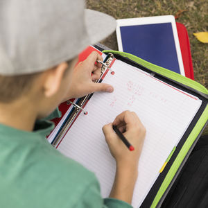 boy in baseball cap writing in notebook outside