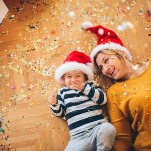 mother and son laying on floor wearing santa hats confetti