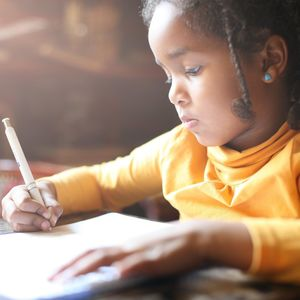 Young Girl Doing Homework Writing on Paper