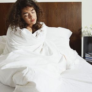 woman in bed wrapped round cover