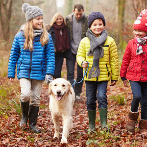 family walking dog in woods