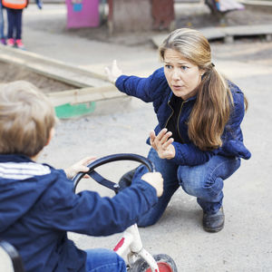 woman scolding boy on tricycle