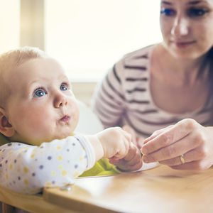 young mom feeding baby in high chair