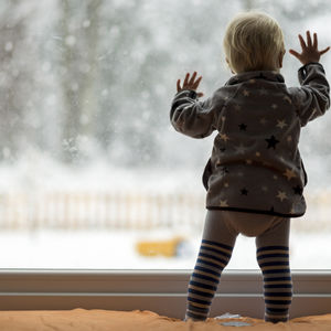 baby girl looking out snowy window