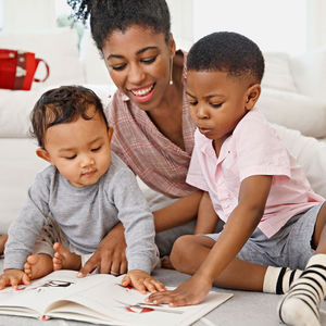 mom reading to two children