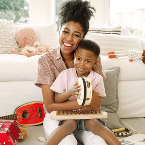 mother and child playing instruments near sofa