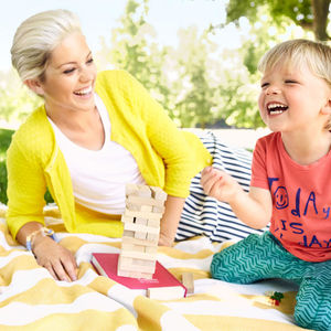 Mother and Child Play Jenga on Yellow Blanket Outside in Grass