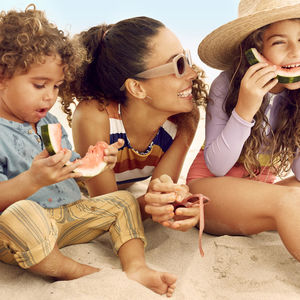 mother and kids at beach eating watermelon