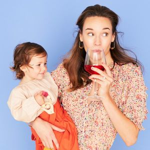 Mother Sipping Glass Red Wine Holding Daughter On Hip