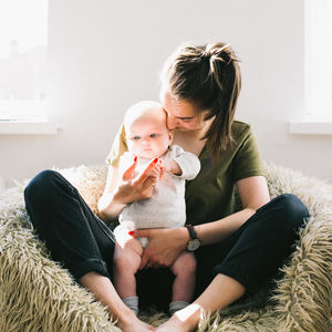 Green Shirt Mother Holding Baby Sitting