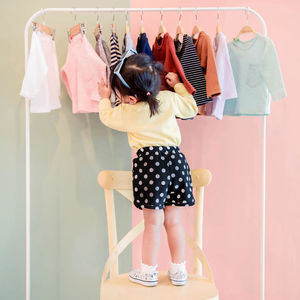 toddler standing on chair looking at clothes on clothing rack