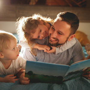 father reading to kids on his back
