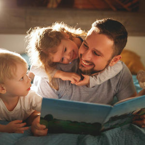 dad with kids at bed time reading book