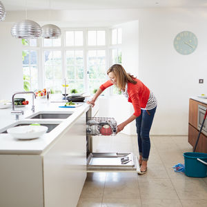 Cleaning Pro Secrets Woman Using Dishwasher in Kitchen