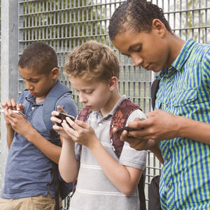 Children Using Cell Phones Leaning on Gate