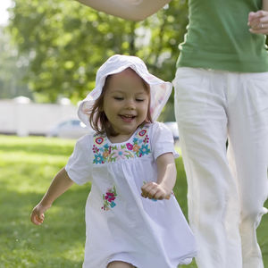 Little Girl Running in Park With Mother Chasing