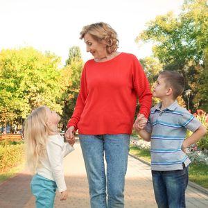 Grandmother With Granddaughter and Grandson Children Walking In Park Holding Hands