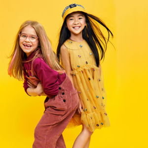 two girls smiling yellow background asian and caucasion