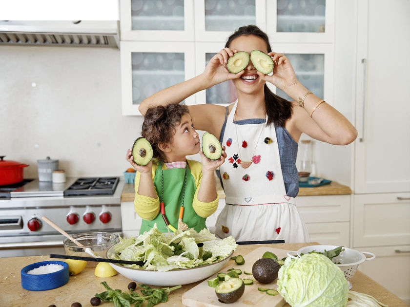 Mother and Daughter Cooking Makes Salad Having Fun Avocado Eyes