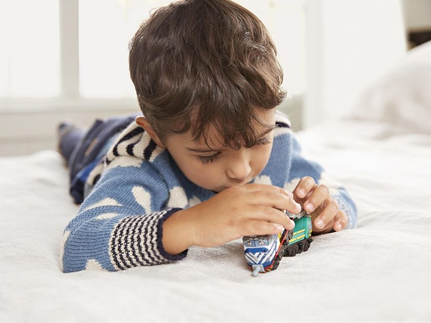 Little Boy Playing With Toy On Bed