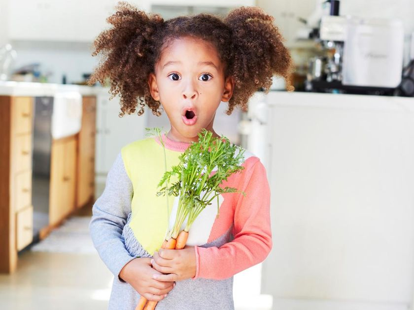 Little Girl Curly Hair Holding a Carrot