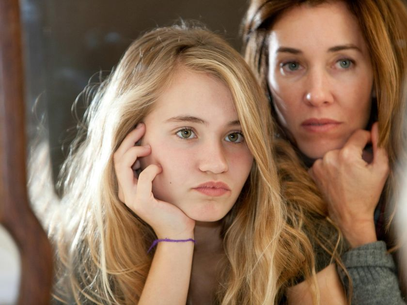 Mother and preteen daughter looking in mirror