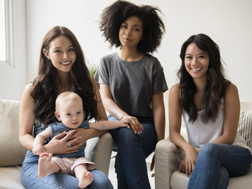 Group of smiling friends with a baby