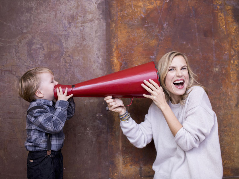 Young boy speaking into megaphone, woman holding megaphone to her ear