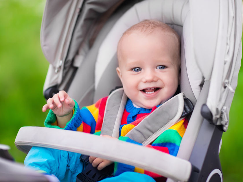 Rainbow-striped baby in a stroller