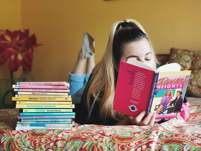 Girl Reading Book on Bed Stack of Books