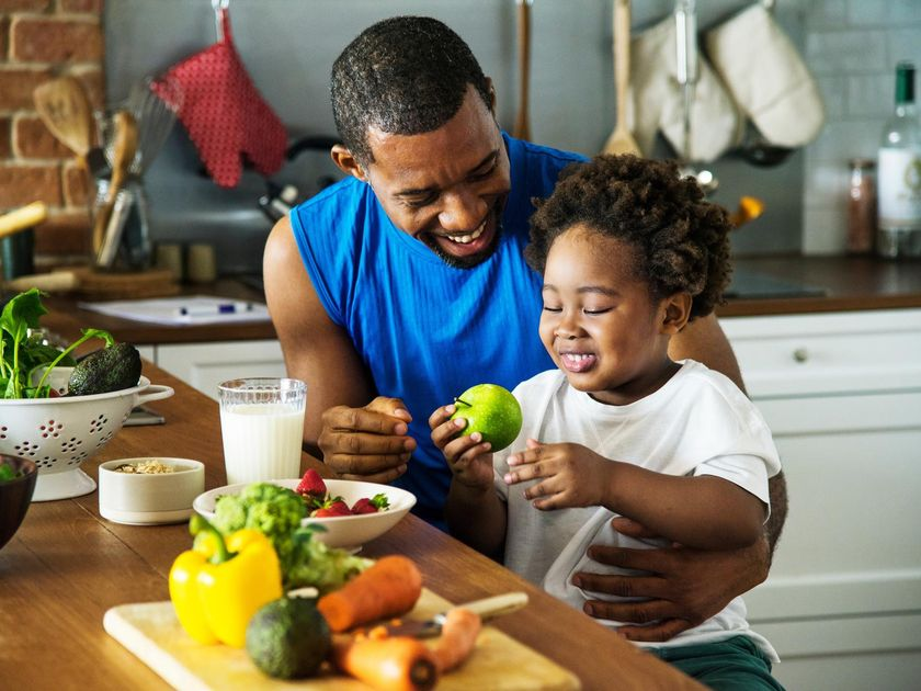 Father and Child Sitting in Kitchen with Healthy Fruit and Vegetables