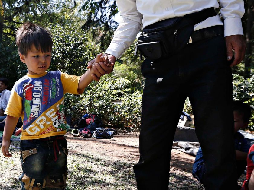 Young Migrant Boy Holding Man's Hand