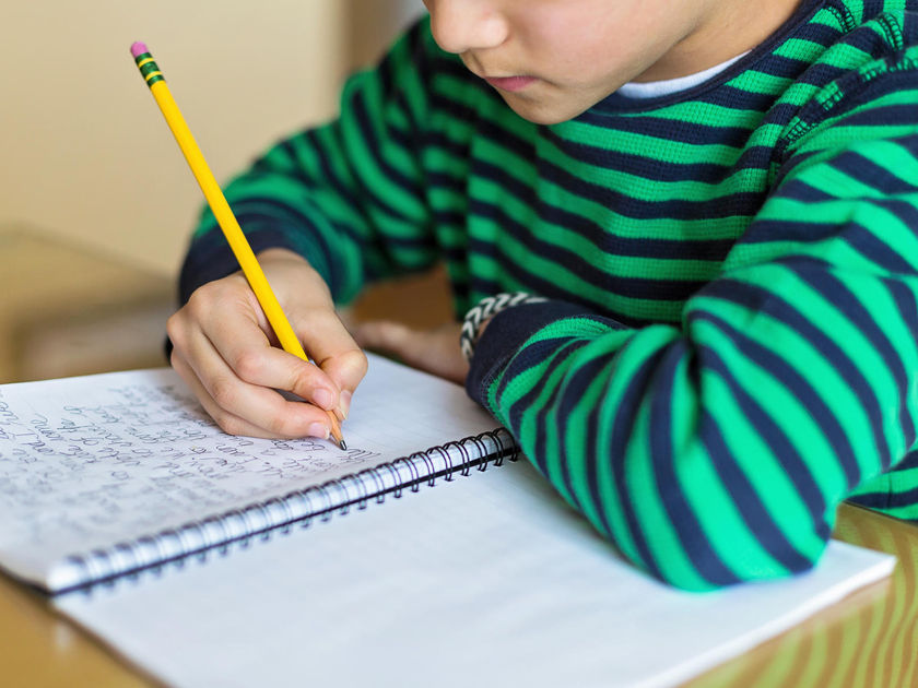 Child Writing Cursive In Notebook