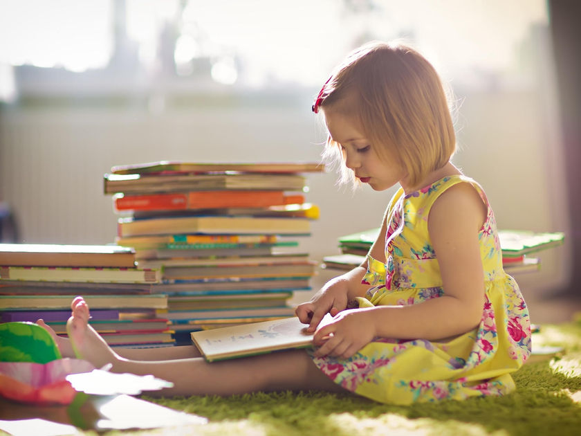 Little Cute Girl in Yellow Dress Reading a Book Sitting on the Floor