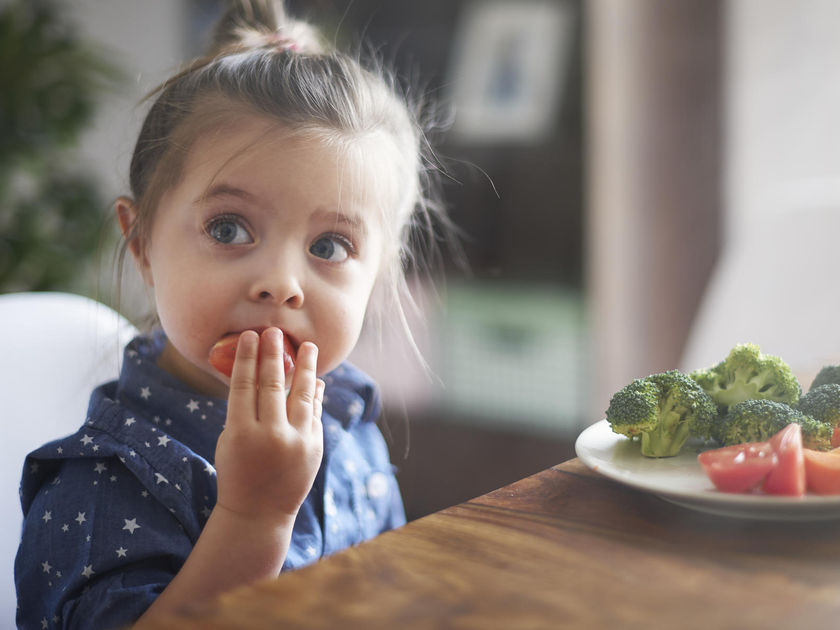 Toddler Girl Eating Tomatoes and Broccoli Blue Eyes