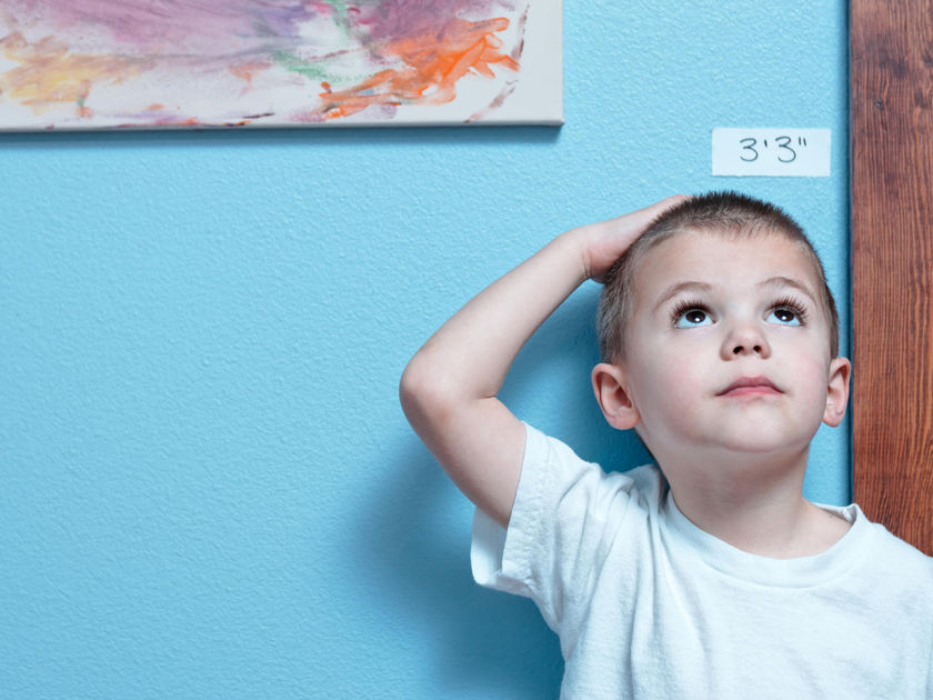 Young Boy Measuring Height on Blue Wall