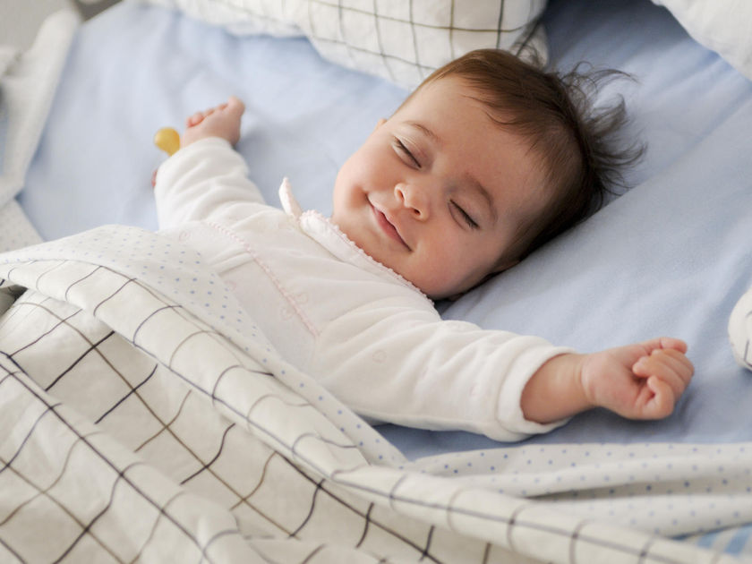 Smiling Baby Lying on a Bed Sleeping on Blue Sheets