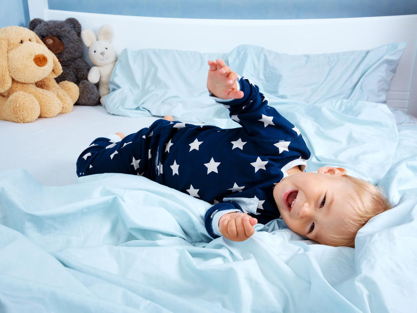 Little Boy Laying On Toddler Bed in Pajamas