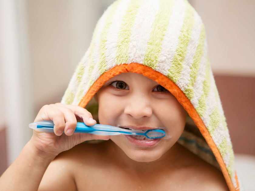 Boy Brushing Teeth Wearing Towel