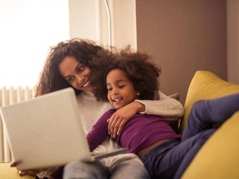 Mother and Daughter Laying On Couch Laughing Watching Laptop Computer Screen