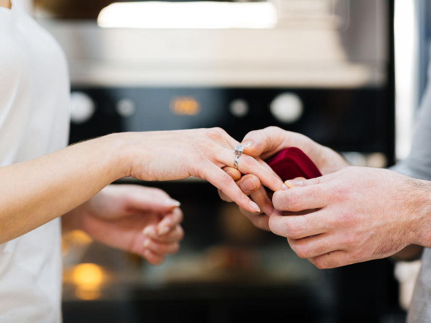 Man Putting Engagement Ring on Fiancee Finger