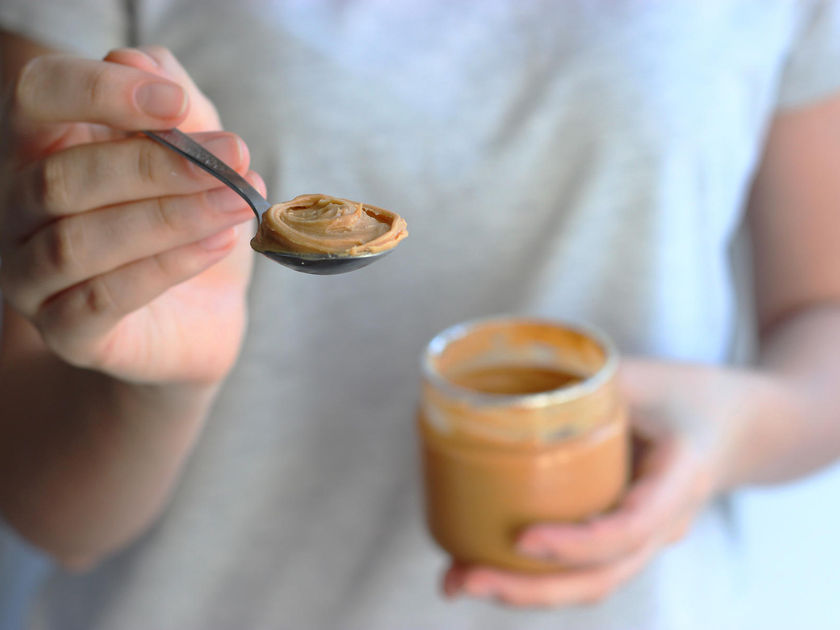 Hand Holding Spoon of Peanut Butter