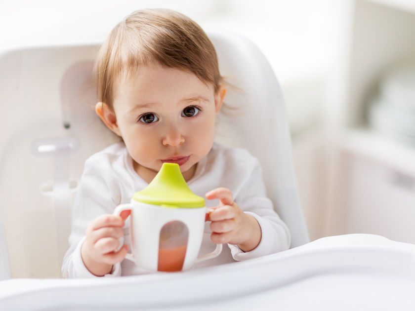 Toddler With Sippy Cup In High Chair