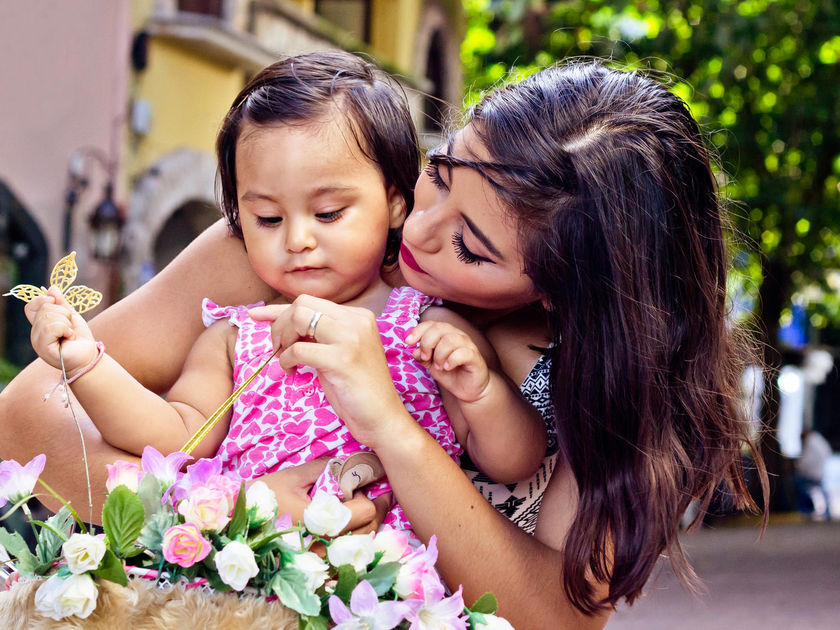 Latina Mom Holding On To Daughter Looking At Flowers